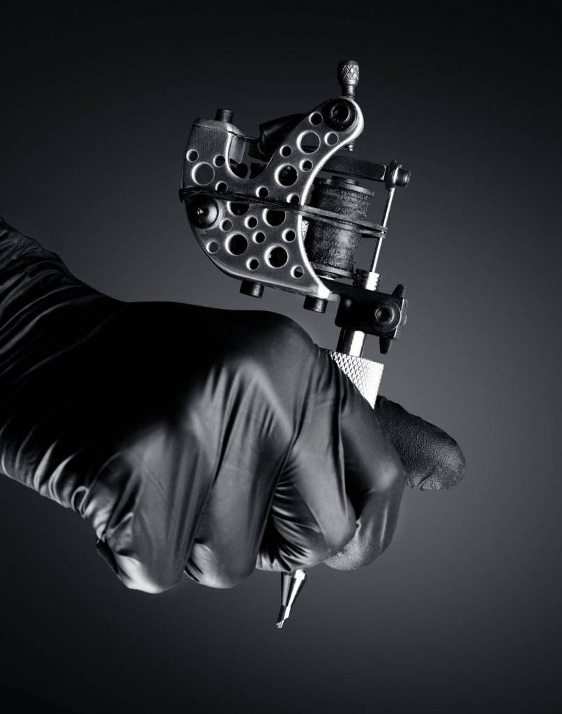 hand holding tattoo machine